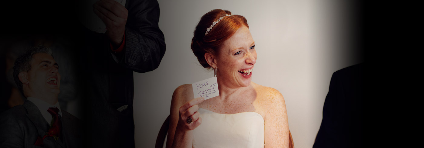 photo of a bride holding a card at the end of a magic trick