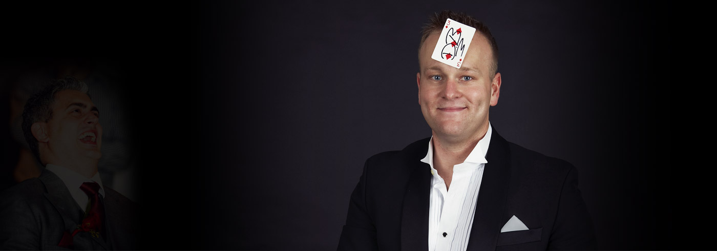photo of magician daniel baker with a playing card on his forehead