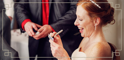 photo of a bride at a wedding taking part in a card magic trick